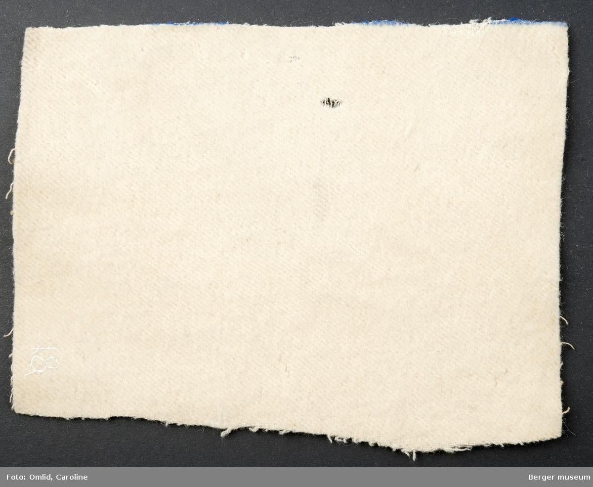 Hvitt teppeprøve. Innslag: ull, Renning: bomull. Avklippet ved den blå stripe. Skitten. Møllangrepet. Liten oljeflekk.