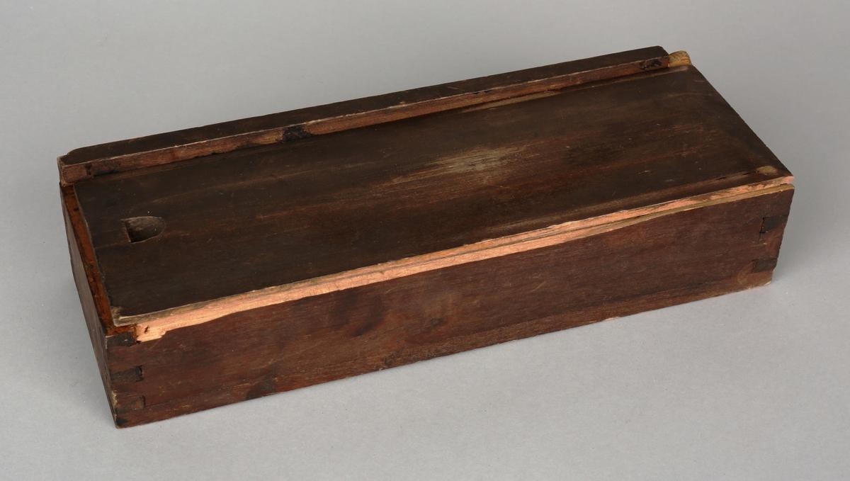 Peileapparat med siktediotere og løs skyggepinn, ligger i liten trekasse med løst lokk.