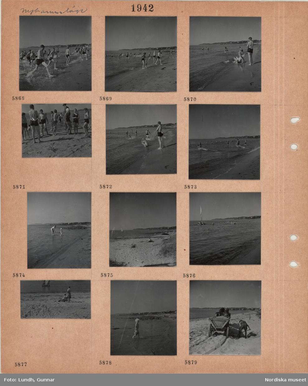 Motiv: Nyhamnsläge, badande pojkar och flickor vid sandstrand, kvinna med litet barn i strandkanten, sandstrand, samhäller i bakgrunden, badande, liten segelbåt, påklädd kvinna och man på sandstrand, litet barn med hink i strandkanten, en man skyfflar sand på en kärra dragen av två hästar.
