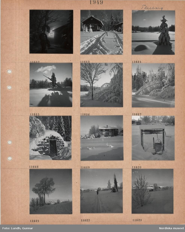 Motiv: Tällberg, julgran med tänd belysning skymtar mellan hus och träd i snö, timmerhus i snö, skidspår framför, snöigt landskap med öppet fält och skog, hopsamlade hässjestörar i snöigt landskap, snö på trädgrenar, jordkällare i snö, timmerhus i snö, brunn med hink i snö, snöigt landskap med gårdsbebyggelse, en person åker skidor förbi hopsamlade hässjestörar.
