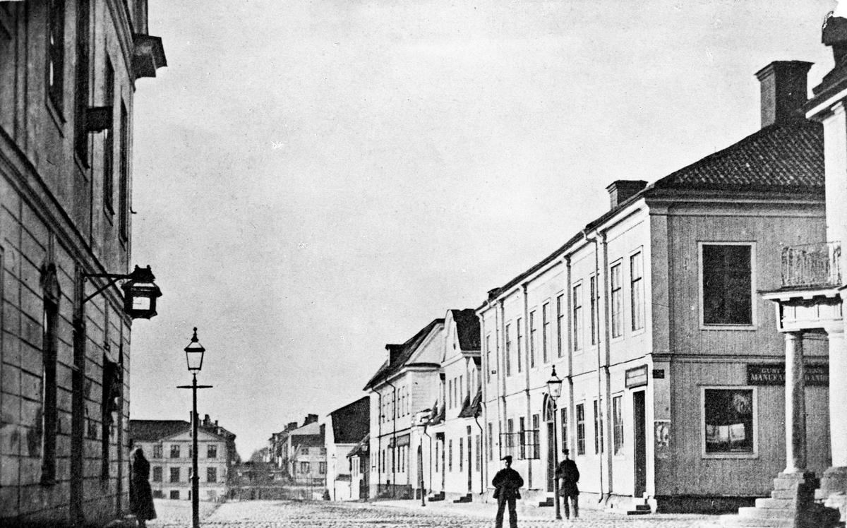 Norra Kungsgatan hörnet av Drottninggatan utsikt söderut. I bakgrunden till vänster Rettigska villan med adress Södra Kungsgatan 1. Bilden är tagen före branden 1869. Huset närmast till vänster står i nuvarande esplanaden.