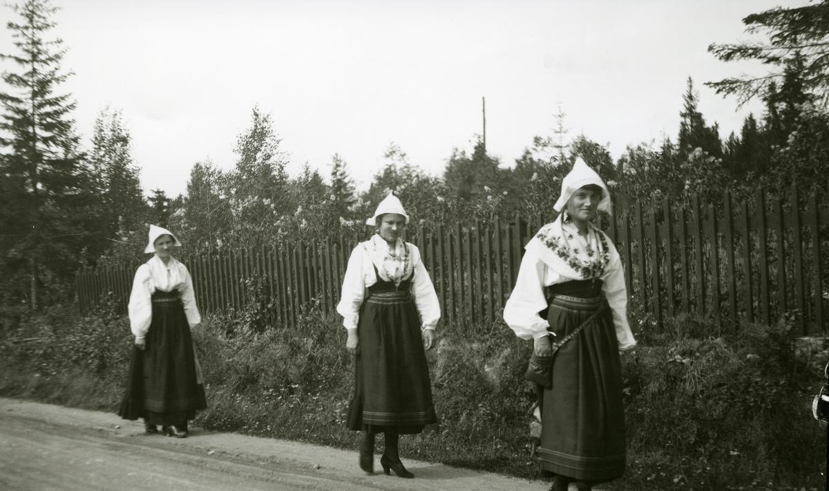 Tre svenske kvinner i bunad gående etter hverandre langs veien i Sverige, v/Siljan.