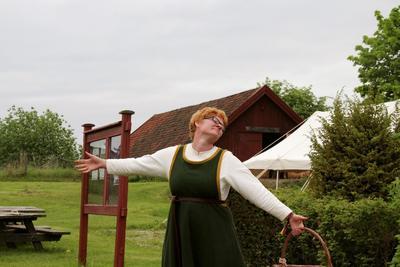 Rødhåret kvinne i middelalderdrakt, med kurv i hånda, slår ut med armene for å ønske velkommen til Urtehagen. Foto/Photo