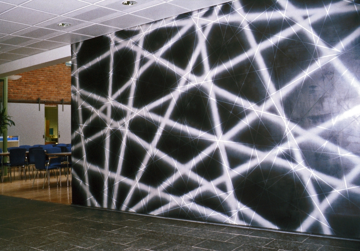 Maleriet er utført rett på murvegg, i ulike strukturer, i romlige skikt mot lysende linjer på en mørk bakgrunn.