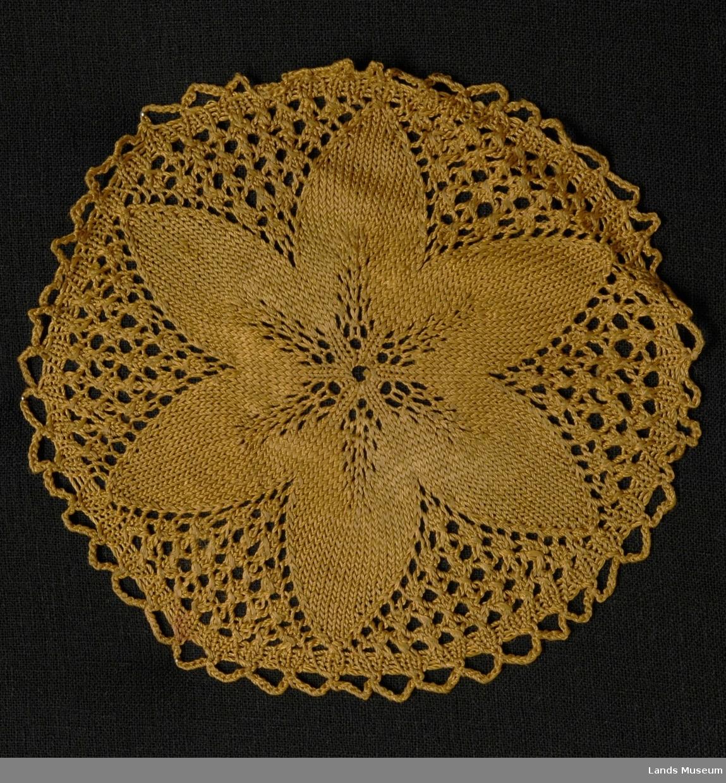 En rund brikke i bronsefarget silke med en blomst til motiv. Kunststrikking.