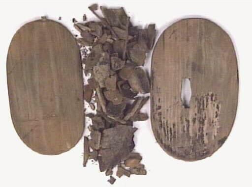 En svepask, i delar. Svepasken består ett lock, en botten samt ett fragmentariskt svep. Locket är försett med ett rektangulärt hål. På vardera sida av lockets ovansida finns bokstäverna LOS eller Ios, ett solkors samt ytterligare ett bomärke inristat. På askens botten finns tre bomärken; två femuddiga stjärnor eller pentagram samt ett timglasliknande märke.