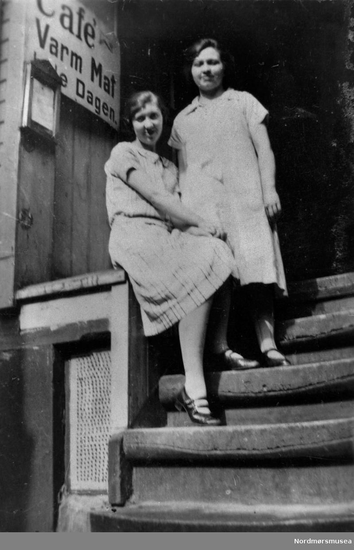 Café, varm mat hele dagen. To jenter i trappa, kanskje gjester, kanskje ansatte. Kristiansund ca 1920.  Nordmøre museums fotosamling