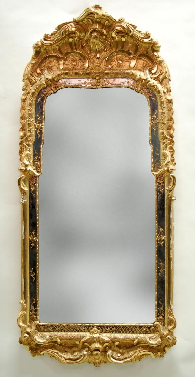 Kat.kort: Spegel, rokoko, skuren och förgylld. Hörnen avrundade. Glaset delvis nytt.