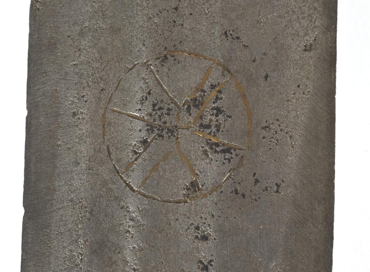 Fasettert rundt knapp med 8 fasetter. Det er innslått 4 smedmerker på knappen, i annethvert felt. Tregrep  Asymerisk åpen parerring med  bøyler med rektangulært tverrsnitt og med kringlefasong med en ytre og en indre parerring. Ytre ring har utsmidde rektangulære partier med kryssfliling. Ytre og indre ring er låst ved at de er tvunnet sammen i senter. Utsiden er smidd som en plateformet deksel. Denne typen pareranordning er trolig norsk Bred tveegget klinge med 3 brodrender på hver side. Klingen er merket med  Solingens løpende ulv, et hjul og 2 andre symboler på begge sider. Klingen er brukket.