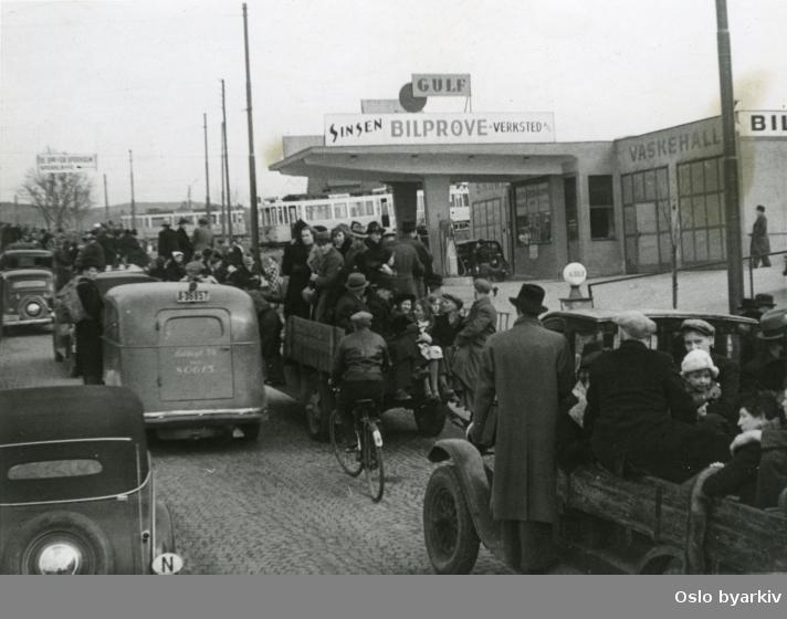 Panikkdagen 10. april etter rykter om bombing av Oslo fra britiske bombefly. Presis klokken 11.30 onsdag 10. april 1940 gikk flyalarmen. Flyktende mennesker på lastebiler, varebiler, personbiler og sykler opp Trondheimsveien på Sinsen ved bensinstasjonen Gulf (Trondheimsveien 197). Den gamle vendesløyfa for Sinsentrikken i bakgrunnen.