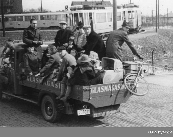 Panikkdagen 10. april etter rykter om bombing av Oslo fra britiske bombefly. Presis klokken 11.30 onsdag 10. april 1940 gikk flyalarmen. Flyktende mennesker på lastebil med reklame for Glasmagasinet. Trondheimsveien med vendesløyfa for Sinsentrikken i bakgrunnen. Bak villabebyggelsen i Lørenveien.