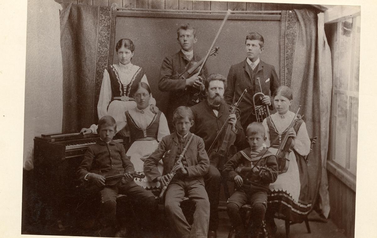 Gruppebilde av en familie med forskjellige instrumenter. De er kledd i bunad/folkedrakt og dresser.