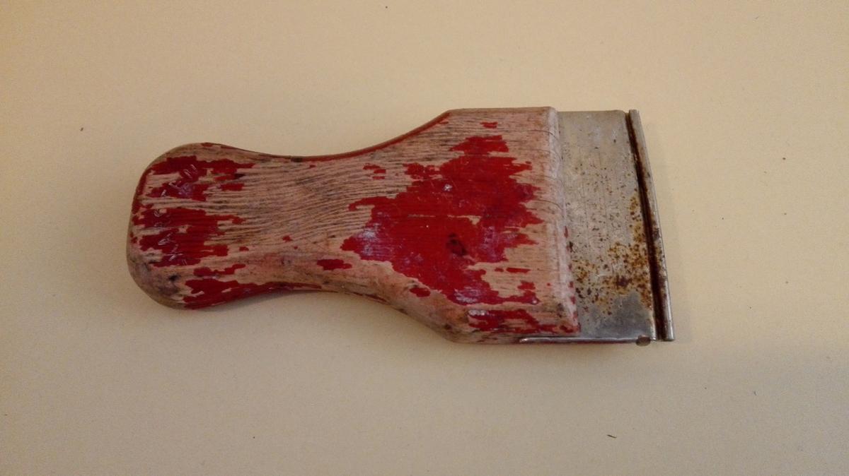 Raudmåla handtakforma treplate, isett stålplate for feste av skrapeblad. Blad manglar. Målingen er delvis sliten bort.