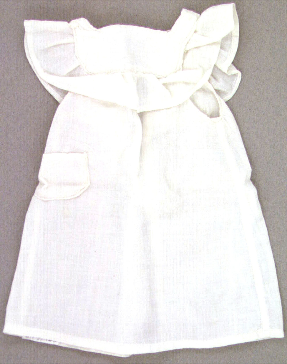 Vit dockklänning, typ förkläde. Maskinsydd av bomullstyg.