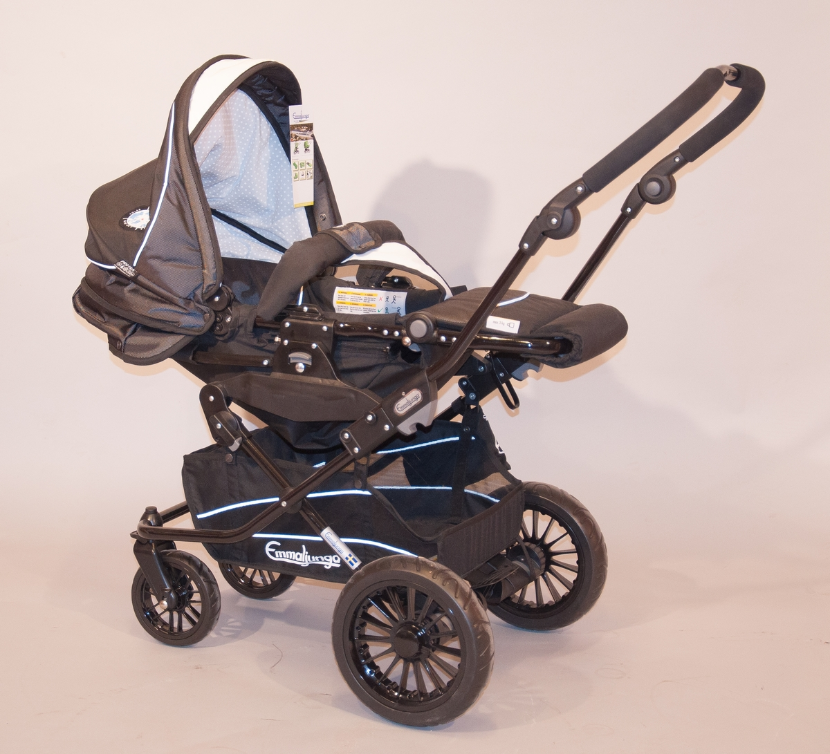 Barnvagn Emmaljunga modell Ozone city.   Chassi av svartlackerad aluminium/plast, med svängbara framhjul och inkapslad kugghjulsbroms på bakhjulen. Punkteringsfria hjul med kullagrade nav. Sits och sufflett i vattenavvisande tyg, regnskydd medföljer vagnen. Sitsen är vändbar. Reflexband i vagnens sömmar. Styret är ställbart för att anpassas efter längden hos den som kör.  Vagnens bredd är 57 cm, vikten på chassi 6 kg och totalvikten i grundutförande 11,3 kg. Det finns 16 färger att välja på, exempelvis Happy Pink, Pro Bordeaux, Black, Pro Coffee, PP Black/Red, PP Navy/White. Denna vagn har färgen Black.