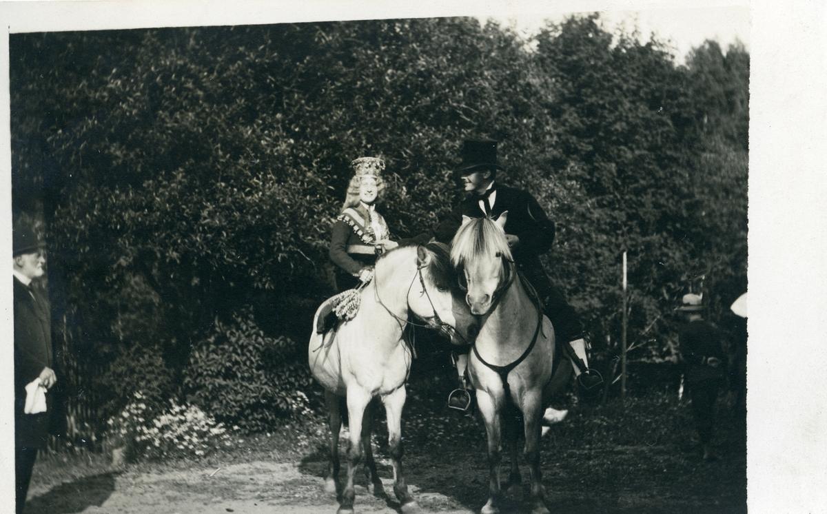 Brudepar til hest i Brandbu. De sitter på hver sin fjording. Bruden har brudedrakt og krone.