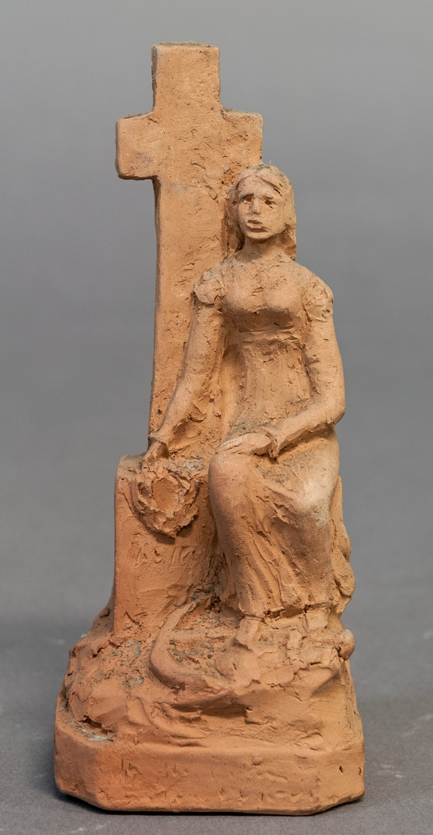 Skiss i terracotta, till gravmonument. Kvinna vid kors.