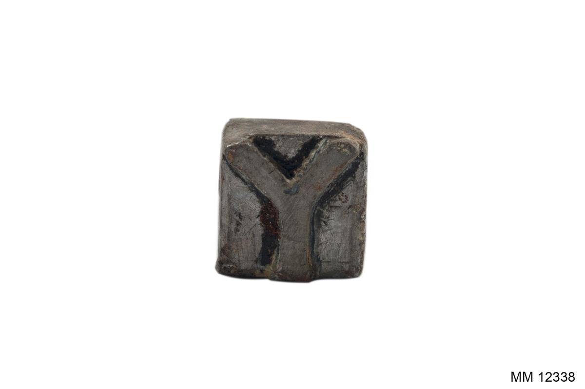 """Stämpel för klädespersedlar. Av vitmetall med trähandtag. Stämpelns utseende: """"Y""""."""