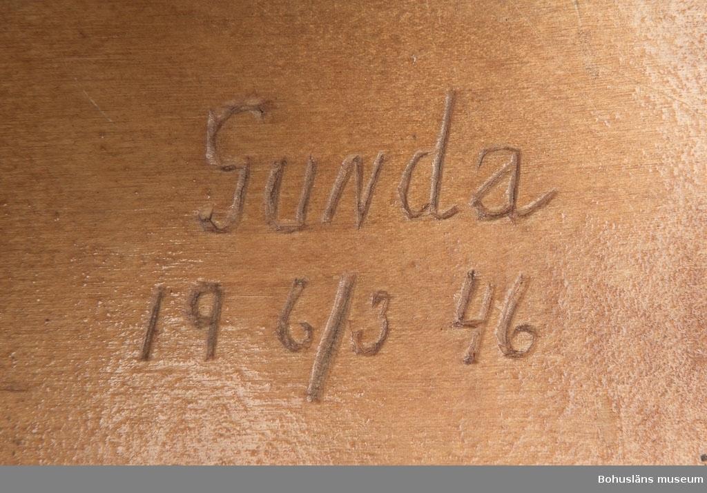 """Skiva av björkplywood med kant av furuträ på tre sidor. Trädelar som inte är tänkta att komma i kontakt med bakprocessen är lackade med cellulosalack. I botten inristat: """"GUNDA 19 6/3 46"""". Tillverkaren morfar till ägaren. Släkt- och personuppgifter se UM026024"""