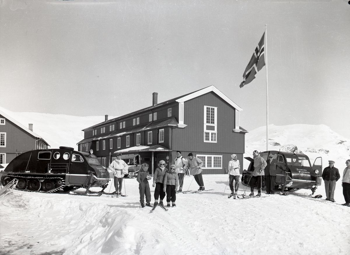 Eidsbugarden hotell med snowmobil og gjester utenfor.