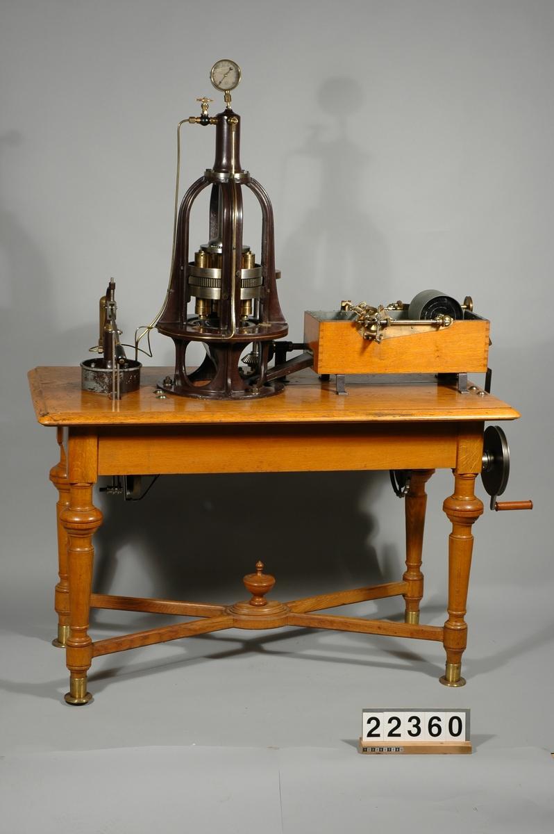"""Maskin för pressning och spinning av garn av nitrocellulosa, konstruerad av R.W. Strehlenert. Monterad på ett bord med låda. Med maskinen följde en härva silkegarn, troligen spunnet på maskinen.  Utställningsskylt om föremålet: """"Maskin för pressning och spinning av garn av nitrocellulosa, konstruerad av R.W Strehlenert och tillverkad i Paris. Tekniska museet"""""""