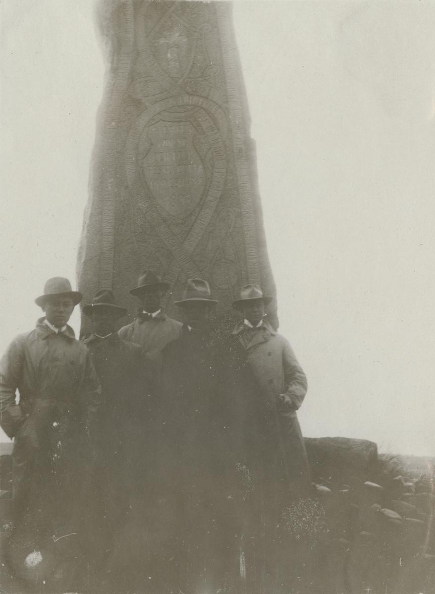Grupp män samlade vid ett monument.