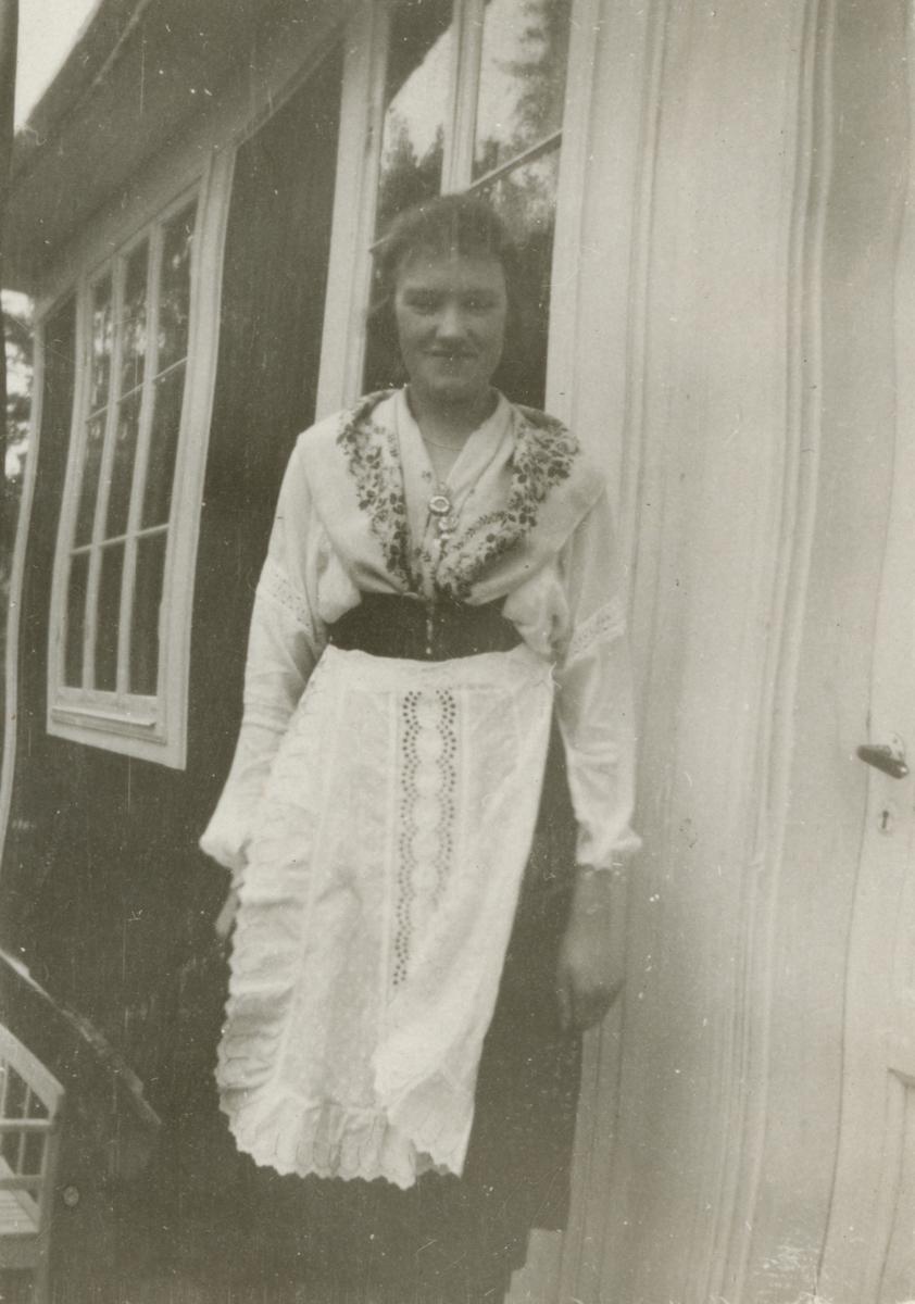 En kvinna framför en byggnad.
