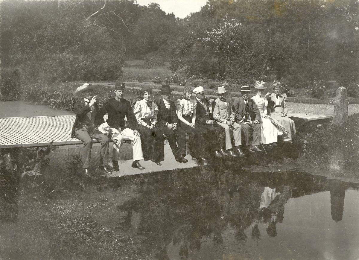 Kvinnor och män sitter på en liten träbro, sommaren 1898. För namn, se bild nr. 3.