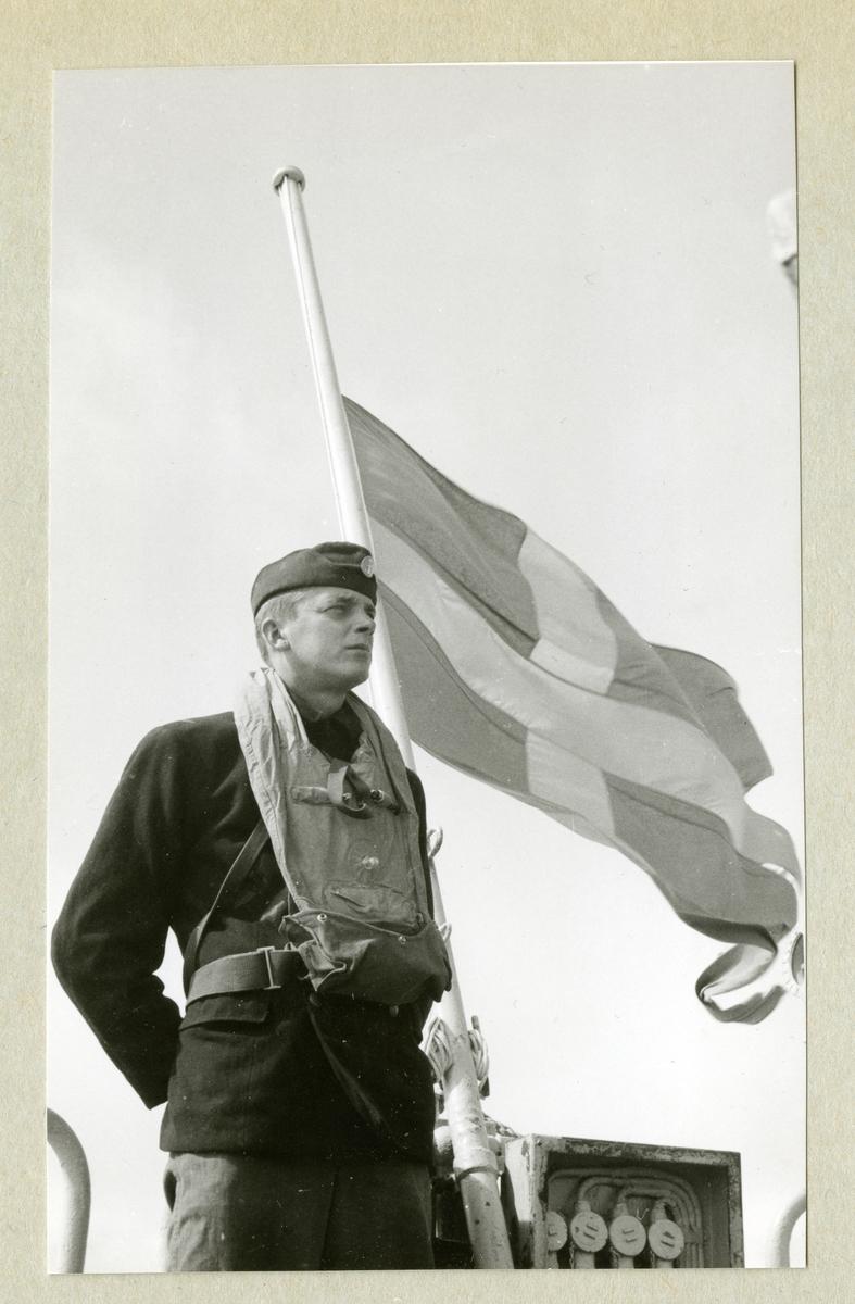 Bilden föreställer en man i uniform som står vid en svensk flagga som vajar i vinden på halv stång. Bilden är tagen i samband med en minnesgudstjänst under minfartyget Älvsnabbens långresa 1966-1967.