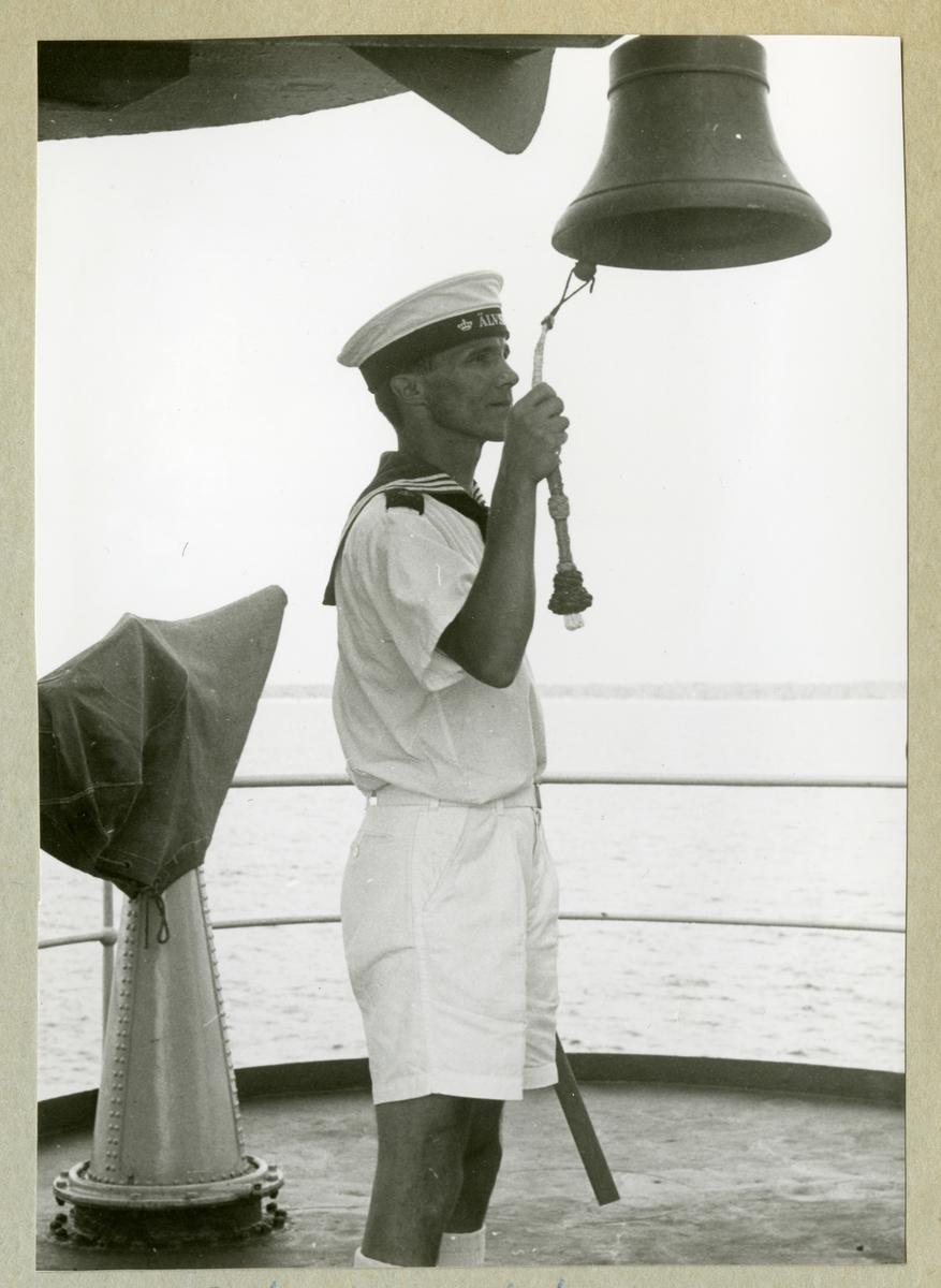 Bilden föreställer en besättningsman ombord på minfartyget Älvsnabben som slår i skeppsklockan iförd sommaruniform under långresan 1966-1967.