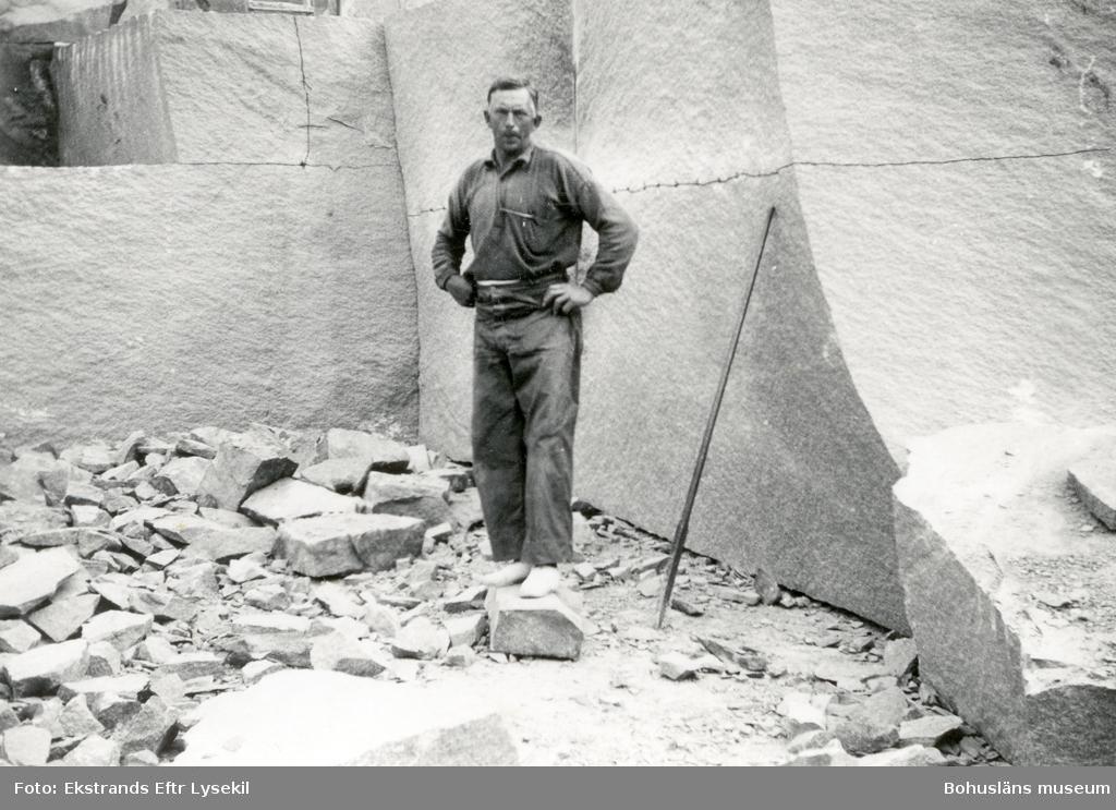 Stenhuggare framför stenblock som sprängts fram