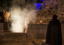 En mørk skikkelse i kappe ser fram mot en hvit engel som står i lys og røyk. (Foto/Photo)