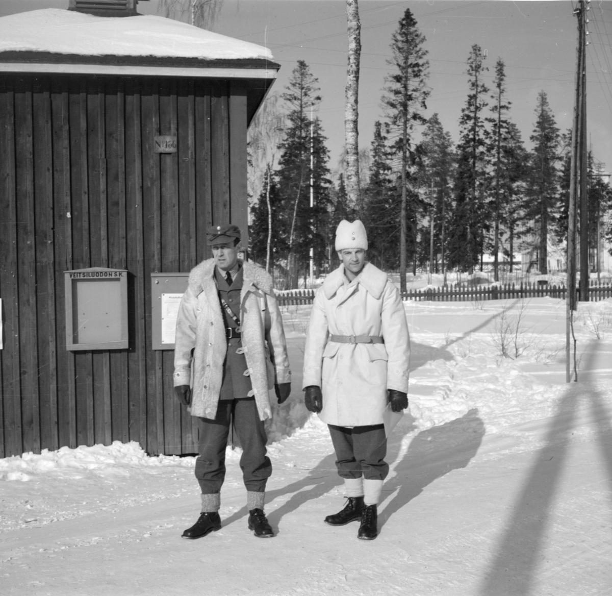 Porträtt. Två militärer tillhörande Svenska frivilligkåren i Finland, F 19 står i vinteruniform vid husvägg. Till vänster Hugo Beckhammar, chef F 19 och till höger Malcolm Hamilton.