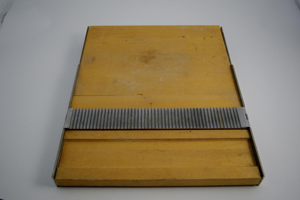 Rektangulært pillebrett (a) av tre med metalldel og tilhørende utstyr: trepinne (b), rotundifikatorer (c-d) og metalldel (e). Pillebrettet har mal for produksjon av piller i to ulike størrelser. En del sitter fast i brettet. Denne har to typer riller og er av metall. En metallgjenstand (e) har tilsvarende riller (en størrelse på hver side). Trebrettet (b) ble brukt til utrulling av pølsen som skal bli til piller. c) og d) er to runde trestykker som kalles rotundifikator. Settet med gjenstander er komplett og ble brukt til produksjon av piller på apoteket.