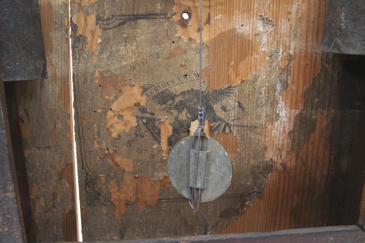 Amerikaklokke i tre med dør foran og innvendig urverk med lodd og pendel. Døren har to glassvindu. Øvre vindu har klokkeskiven bak og nedre vindu med dekor.