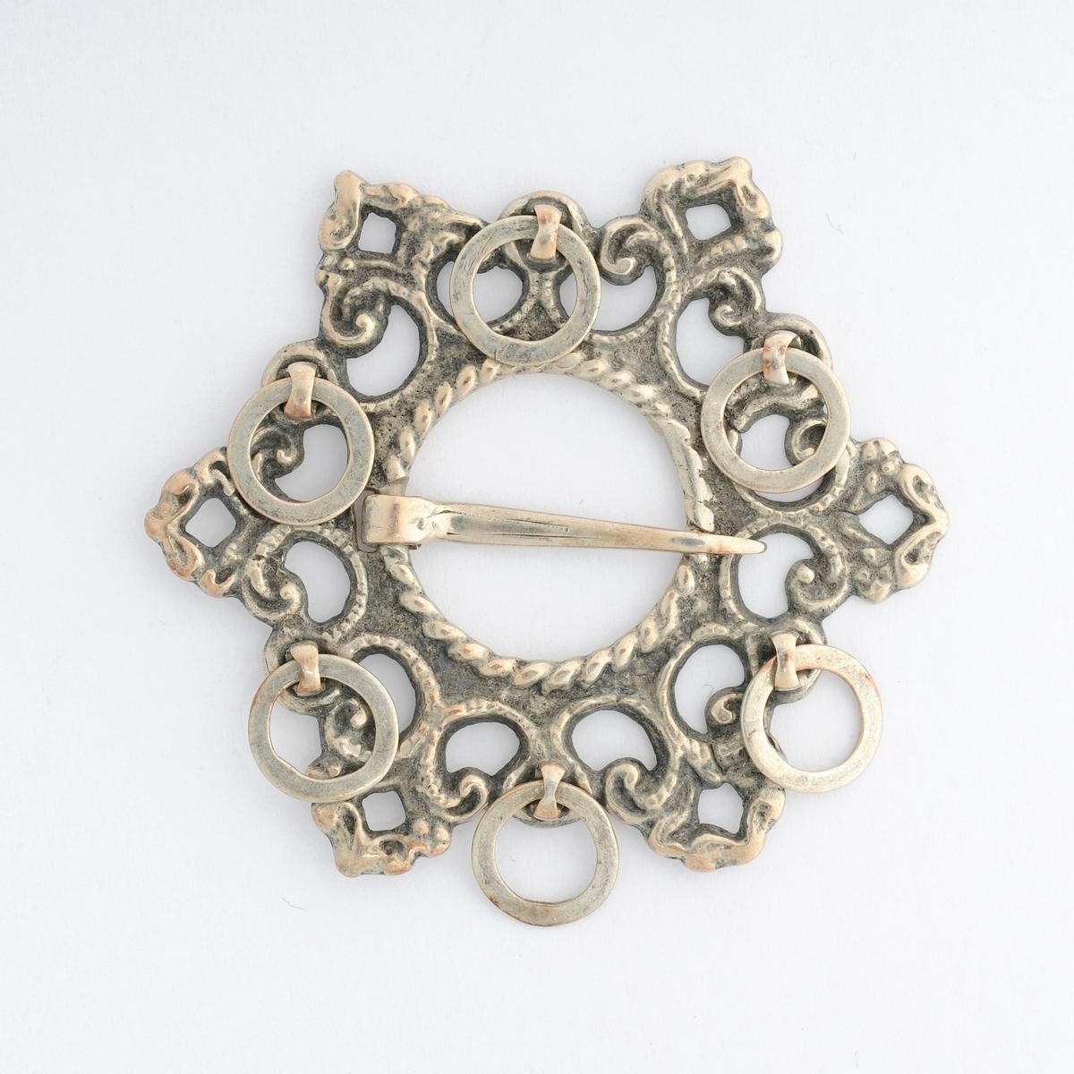 Sporesølje (spiresølje) støypt i sølv med seks spir og seks ringar. Open tann (nål).