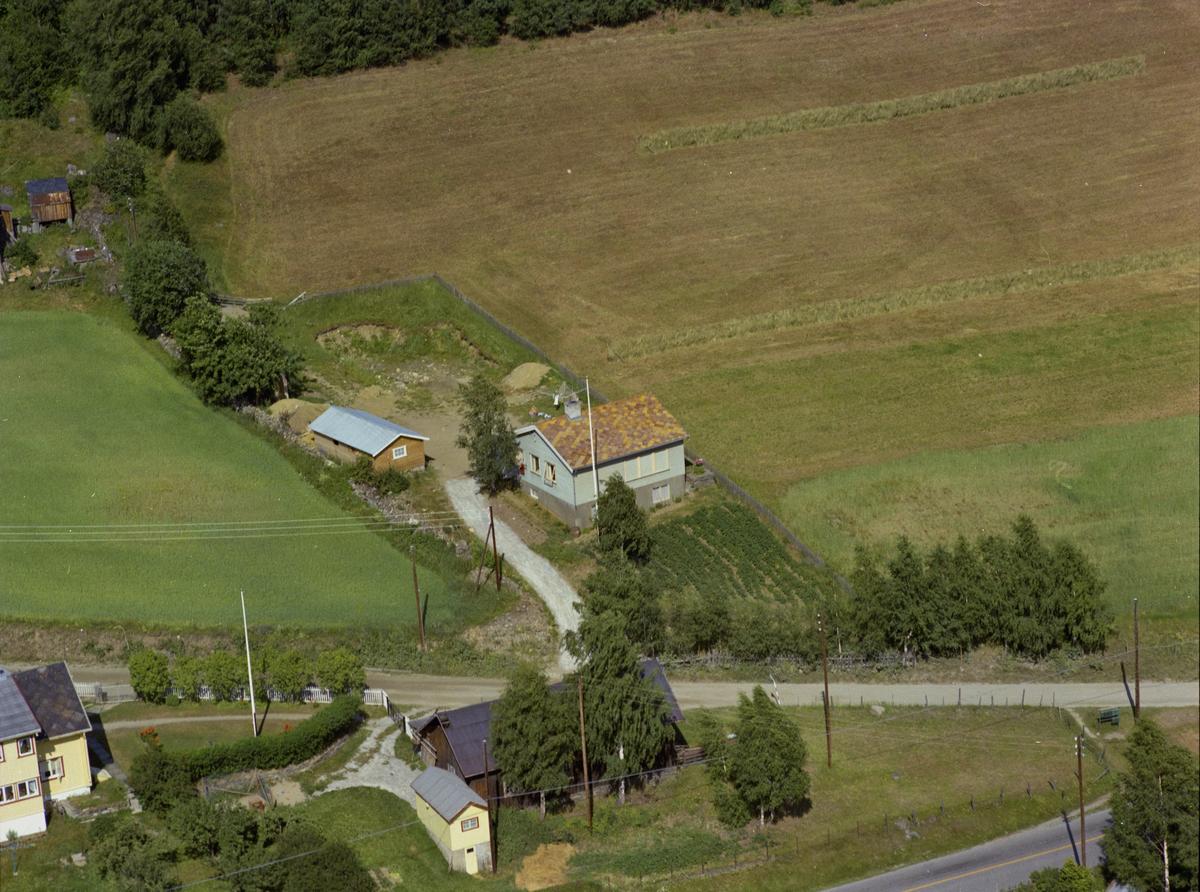 Sør-Fron, Hundorp. Lyseblått hus med potetåker og hvit flaggstang, antagelig Bjørkhaug i Eksisvegen 2. Jensbakk i nedre venstre hjørne.