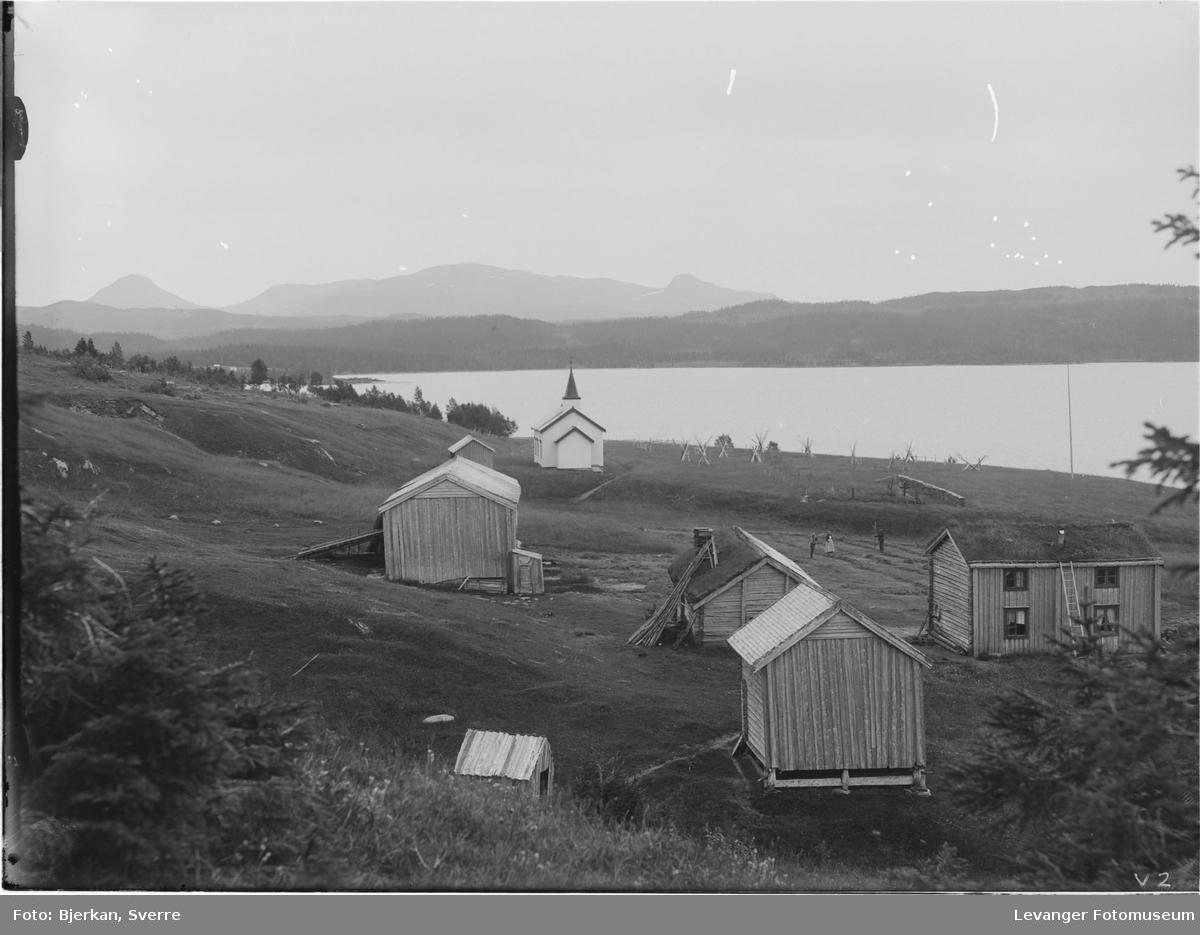Vera kirke, kapell ved Veressjøen i Vuku med gårdsbruk foran.