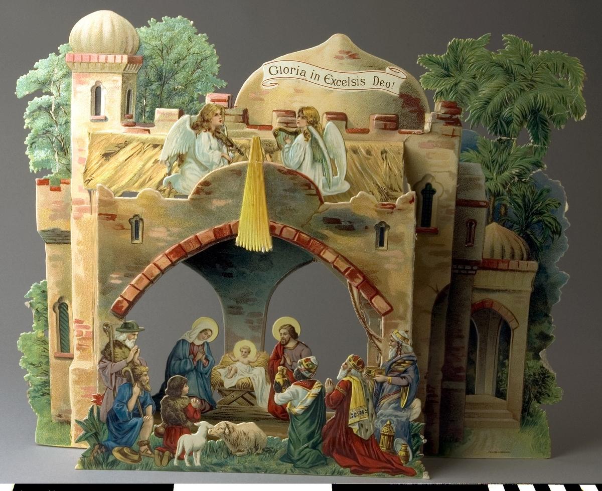 Julkrubba av papp, fabriksgjord. Krubban består av tre delar av motivtryckt  glansig papp i många färger, som fogas samman i djupled. Motivet är Jesu födelse i ett stall i Bethlehem, med herdar, änglar och de tre konungarna. Den bakersta delen har utskurna försteröppningar, försedda med röd cellofan. I det nedre högra hörnet tryckt: PRINTED IN GERMANY.  Stjärnan har fallit bort, endast dess strålar finns kvar. Nötta kanter och brytmärken, men annars i tämligen gott skick.