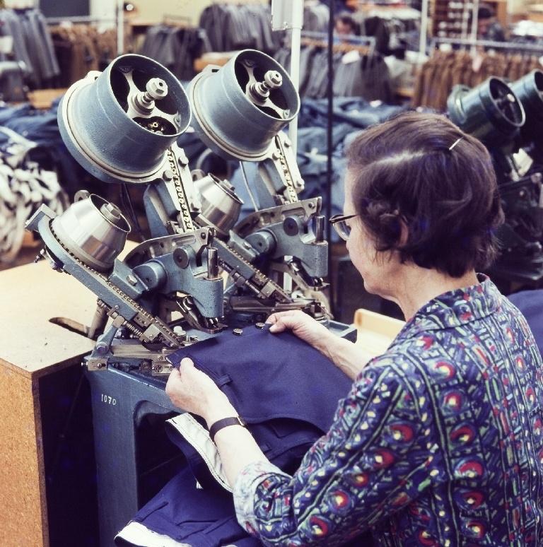 Kvinnelig arbeider isette patentknapper på arbeidsklær/jeans med hjelp av en automat i konfeksjonsfabrikken til Jonas Øglænd Sandnes.
