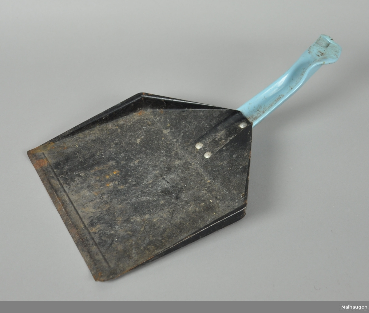 Peisspade av metall, med hanke av blå plast. Enden av håndtaket har smelteskader.