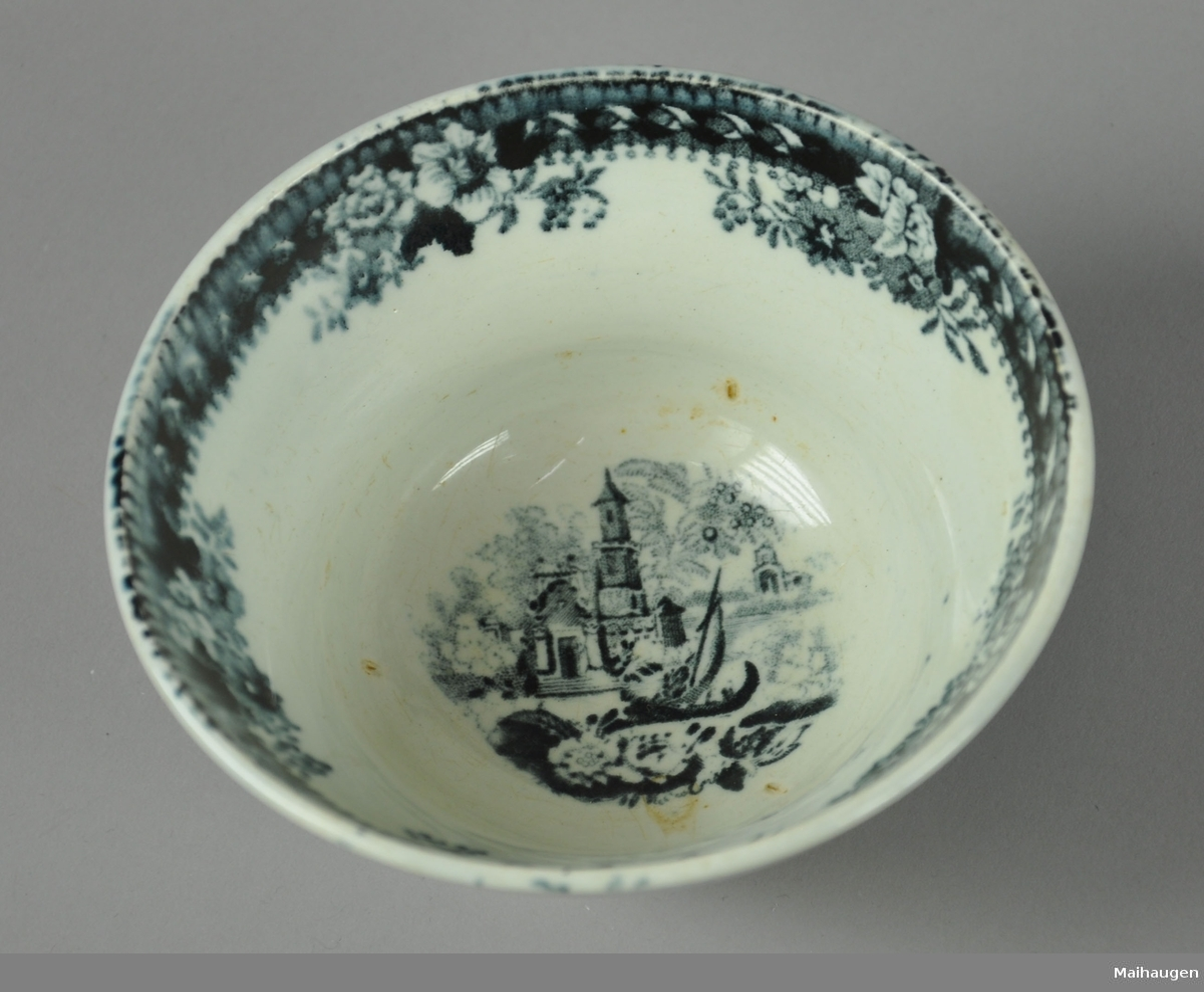 Rund skål av glassert keramikk, med malt dekor. Motiv på dekor av båt på elv ved bygninger.