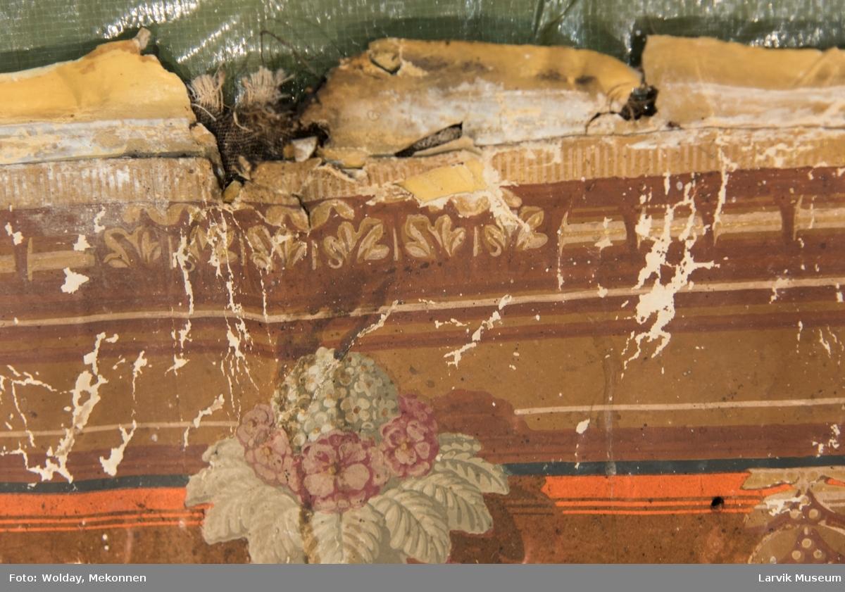 """En bred tapetbord øverst og en mindre nederst. Den øverste har motiv i form av en """"girlander"""" med fuglemotiv i midten. Den nederste, smale: Tekstilbord med blomster. Signatur på forsiden og 2 stempler på baksiden. Motiv: Blomsterkrans med en krone på toppen og tre i midten"""