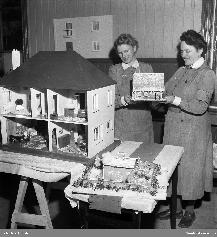 Julmässa hos lottorna i Timrå. Två kvinnor visar upp pepparkakshus och dockskåp.