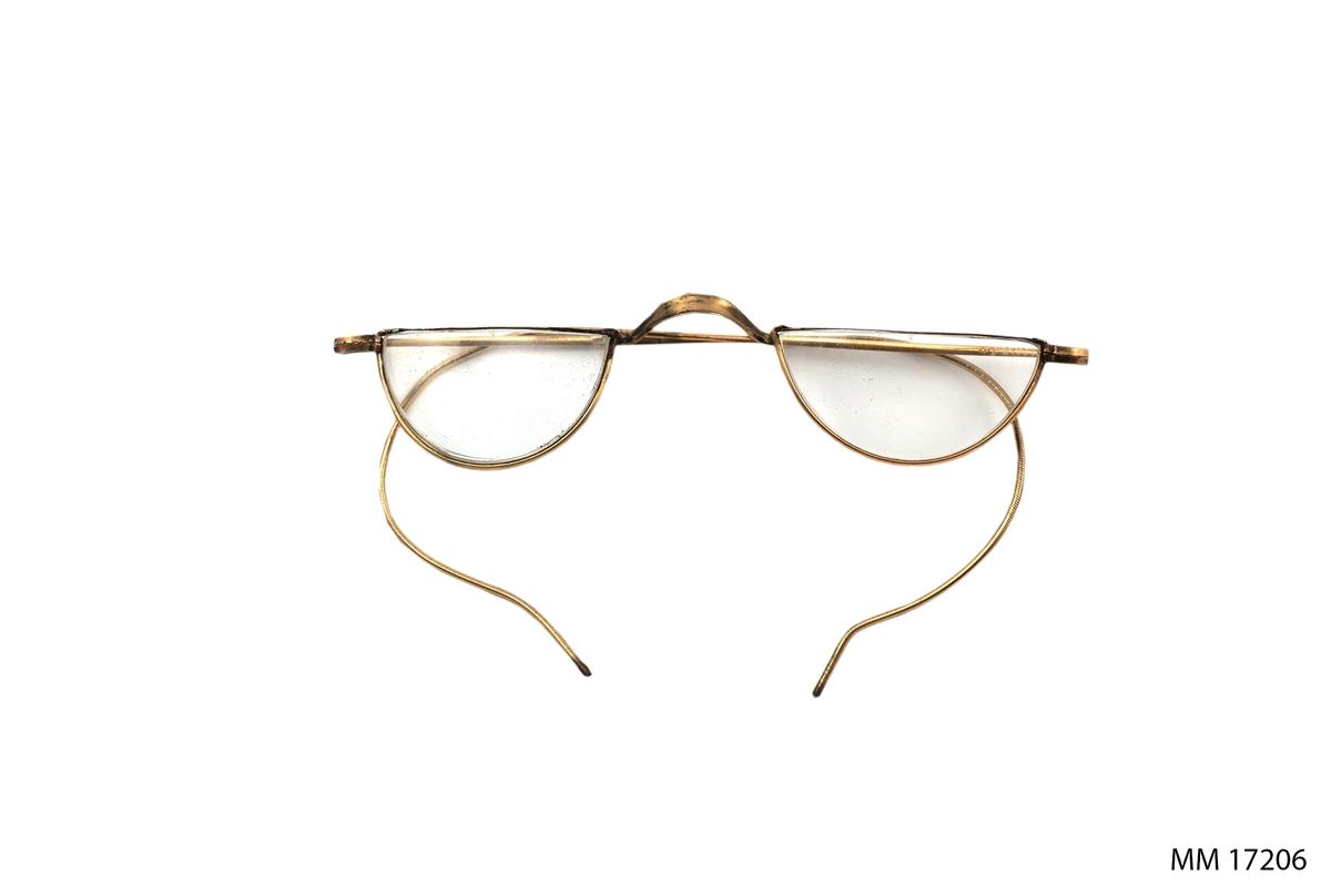 Glasögon med tunna metallbågar (mässing? ). Glasen är halvcirkelformade, skalmarna ledbara runt öronen.