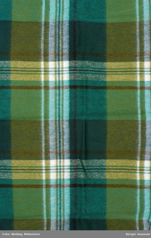 En pleddprøve i rutemønster. Prøven er klippet på tvers, slik at prøvens kortsider har jarekant  Mønsteret karakterisereres av rutemønster i rektangulære felt av varierende størrelse,  med smale striper horisontalt og vertikalt. En definert stripe med hvit renningstråd skaper tyldeige firkanter som er oppdelt av smale striper som krysses i firkanten. Uten frynser. I grønntoner.