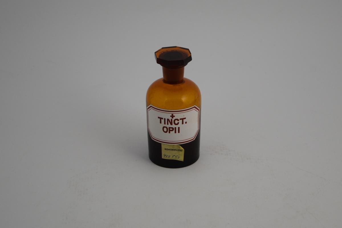 Brun glassflaske, smal hals, åttekantet glasspropp. Påsatt hvit etikett med rød skrift og ett rødt kors, noe som indikerer at innholdet i krukken er giftig. Krukken har blitt brukt til oppbevaring av opiumstinktur. Nå tom.