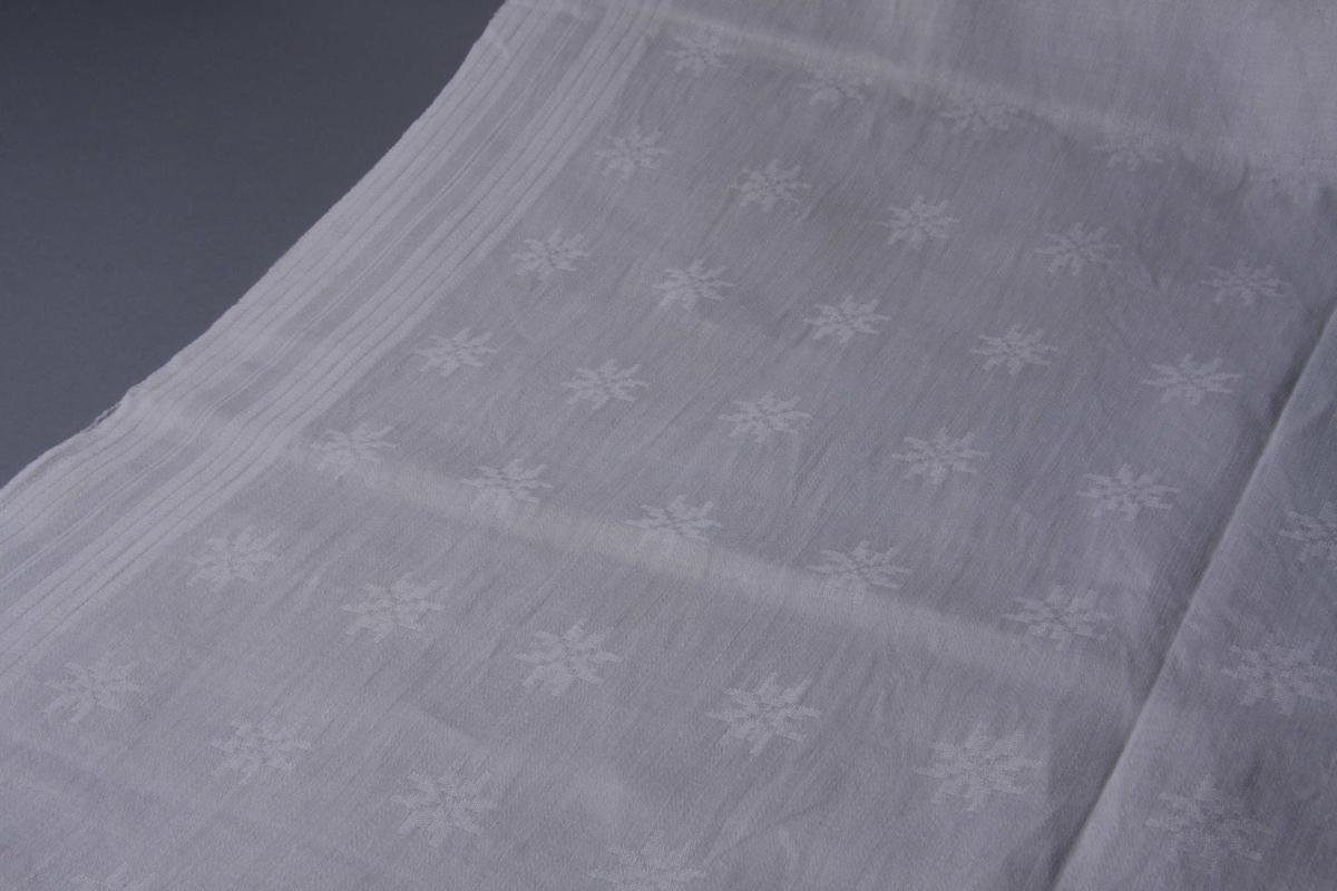 Grov hvit lindreil i to bredder sydd sammen på midten. Mønster av 8-bladsroser, stripemønster langs sidene. Smal fall på kortsidene.