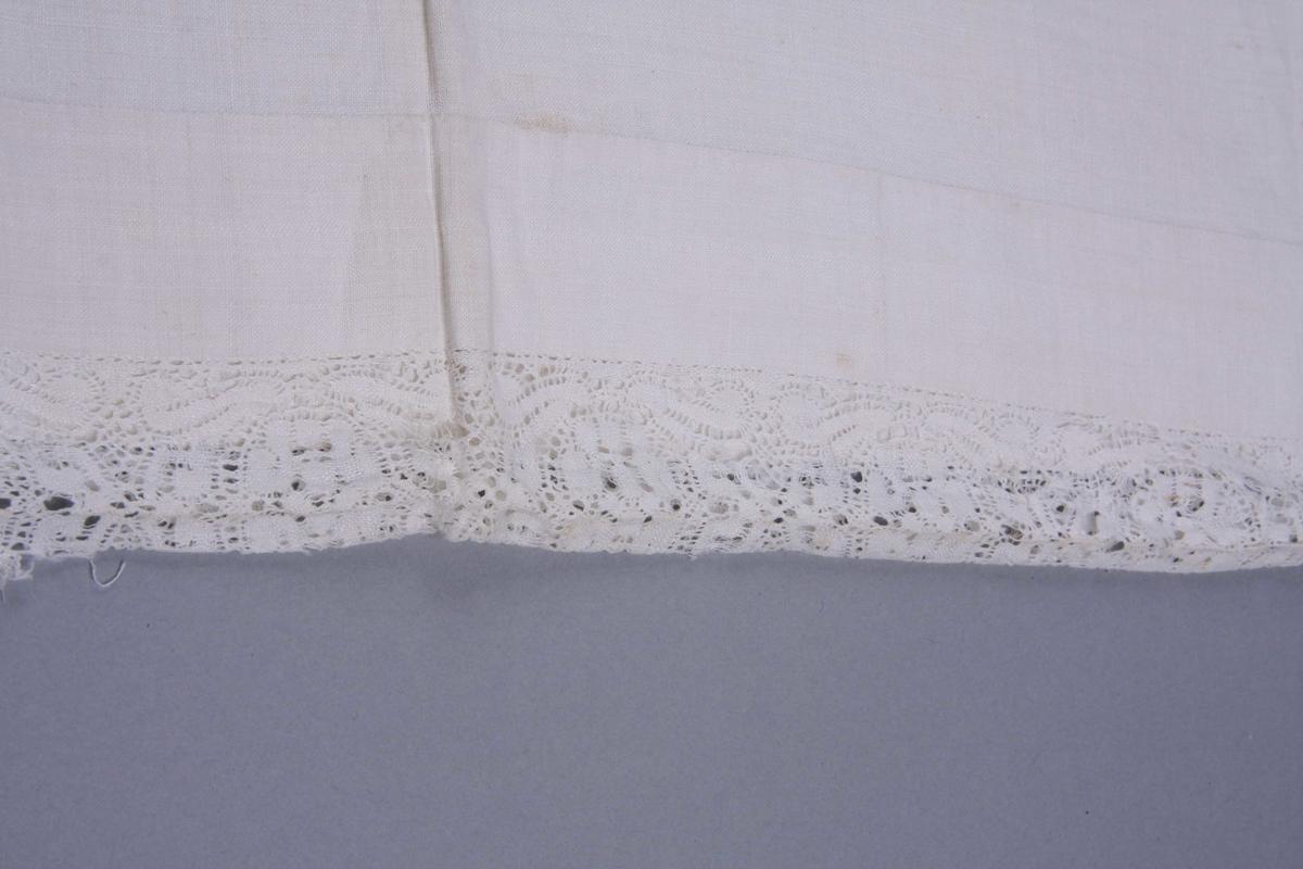 Hvit linlerret åpent i den ene kortsiden med smal fall og knytebånd. Den annen er sydd sammen med en 5 cm. bred knipling, meget fin med mønster av bølgete bånd og ovale medaljonger. Kniplingen meget defekt.