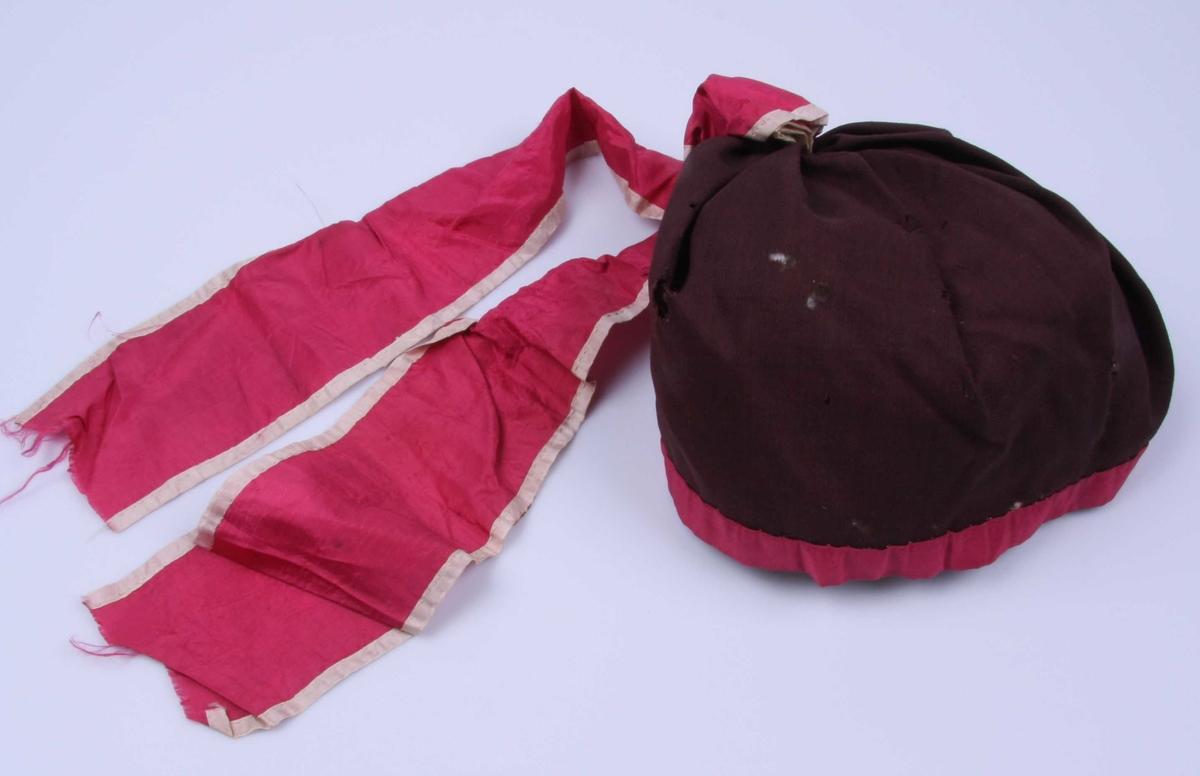 Av tynt brunt ullstoff, kantet med bånd. Silkebåndet danner her en oppstående sløyfe på midten. Tøystykket er 21 x 59 cm. Silkebåndet er 3,5 cm. bredt.
